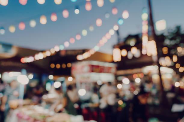onscherpe achtergrond bij nacht markt festival mensen lopen op weg. - traditioneel festival stockfoto's en -beelden