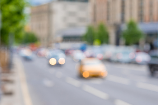 Blurred background - city road and orange taxi