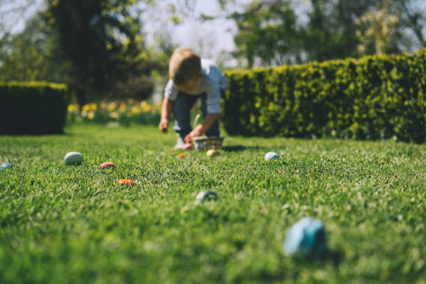 Blurred background. Little children gathering painted decoration eggs in spring park. stock photo