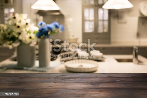 607472268 istock photo Blurred background. Modern kitchen with wooden tabletop and space for you. 975215788