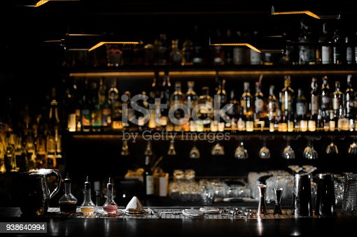 1013514594istockphoto Blurred background of dark bar with barman essentials 938640994
