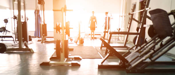 blurred background of gym. - health club stock photos and pictures
