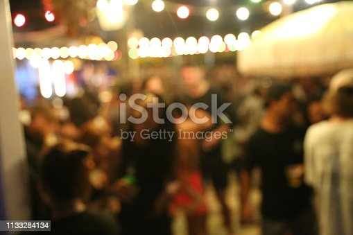 613897214istockphoto Blurred background of many people had fun at a beach party 1133284134