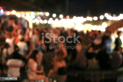 Blurred background of many people had fun at a beach party. Festive concept.