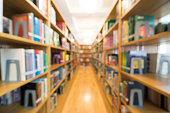 Blurred background of public library, bookshelf with books, diminishing perspective, education concept