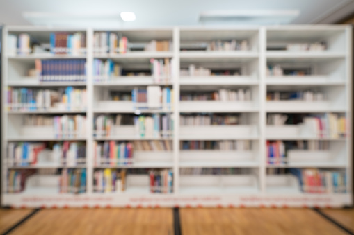 Blurred background of public library, bookshelf with books, education concept