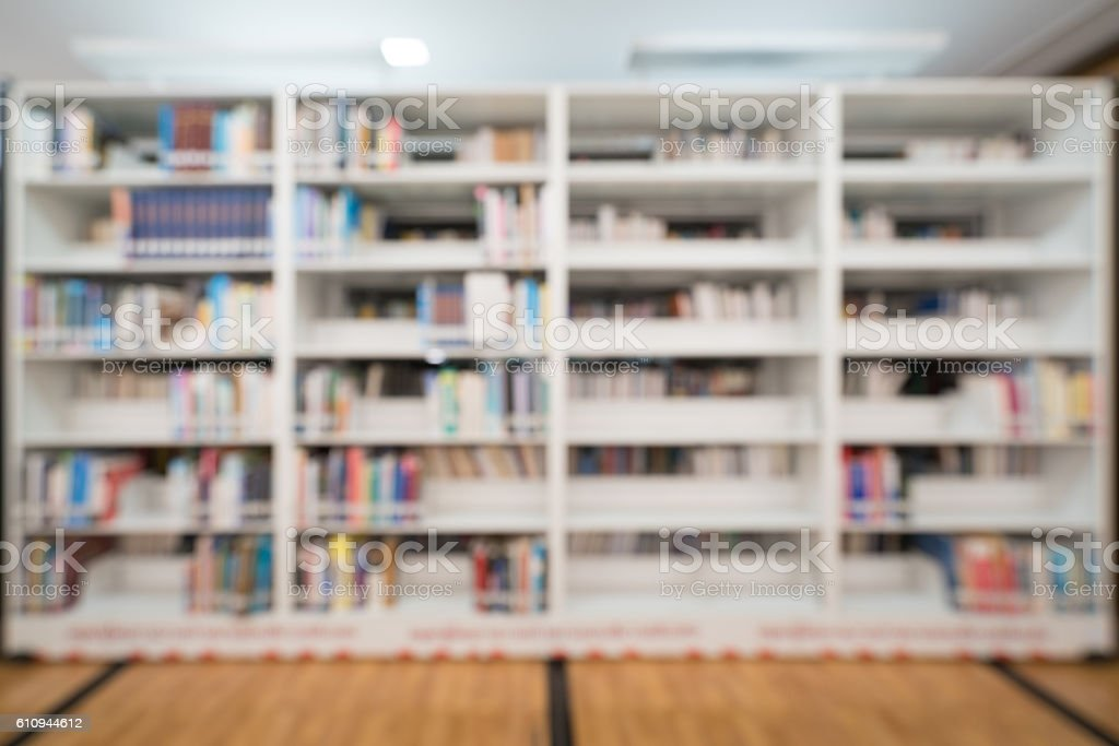 Blurred background of public library, bookshelf with books, education concept stock photo