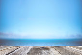 Blurred background of sea coast and old table of wood