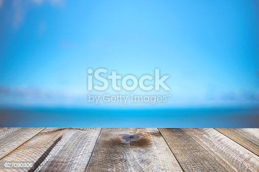 istock Blurred background of sea coast and old table of wood 627090306