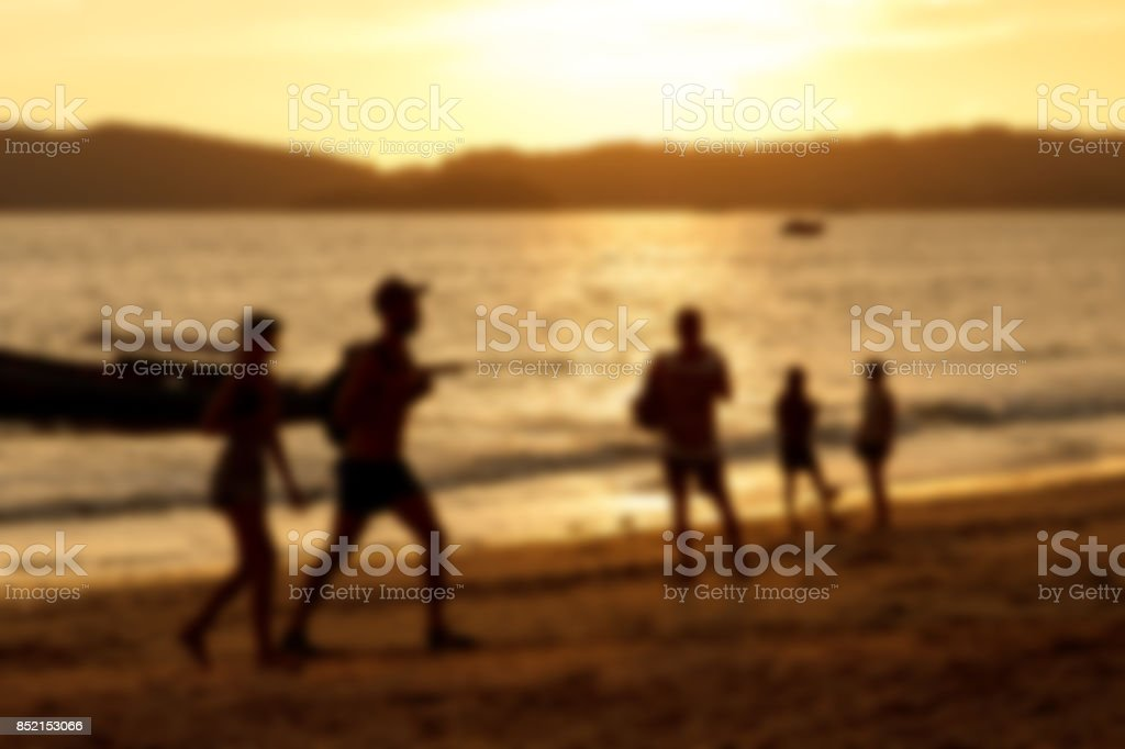 Blurred background of silhouette couple on beach when sunset tine stock photo