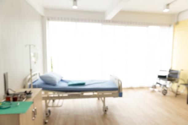 Fondo borroso de la habitación del paciente con una silla de ruedas, cama y la luz de la ventana. - foto de stock