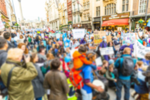 blurred background of thousands people marching in london - protestor stock pictures, royalty-free photos & images