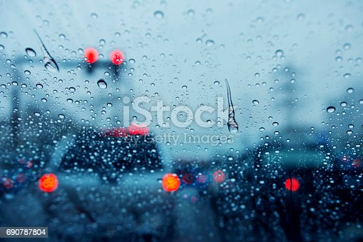 istock Blurred background of traffic jam on rainy day at crossroad junction street in Bangkok with many red light, Selective focus on rain drop, Dark blue tone 690787804