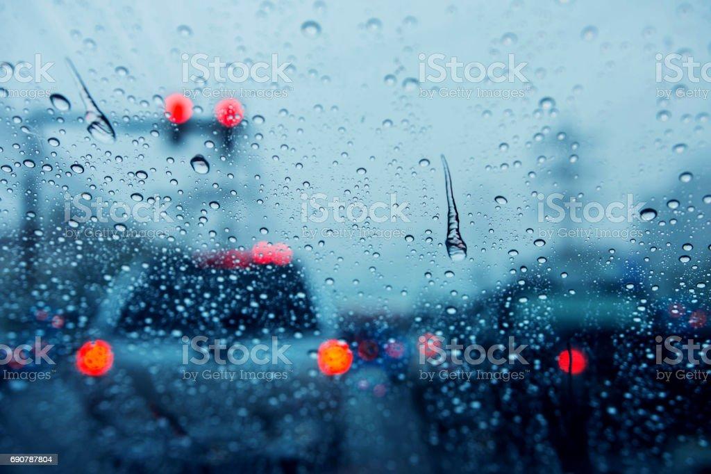 Fondo borroso de atasco en día lluvioso en cruce cruce calle en Bangkok con muchos enfoque selectivo, luz rojo en gota de lluvia, el tono azul oscuro - foto de stock