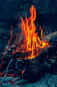 Blurred background. Small flame dying fire, bright red-orange flame. Cozy warm atmosphere by outdoors campfire recreation, burning wood, embers. Vertical photography.
