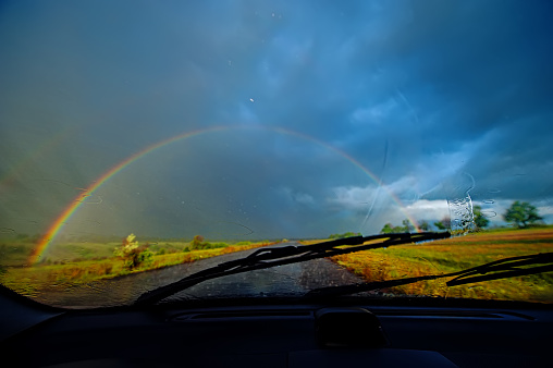 Blurred background, view of a car windshield and landscape and rainbow during heavy rain.