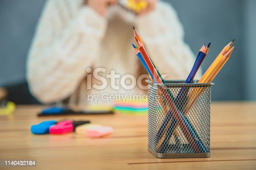 818512928istockphoto Blurred background, where the schoolgirl is sitting keeping her hands up. Stack of pencils of different colours is in the foreground. 1140432164