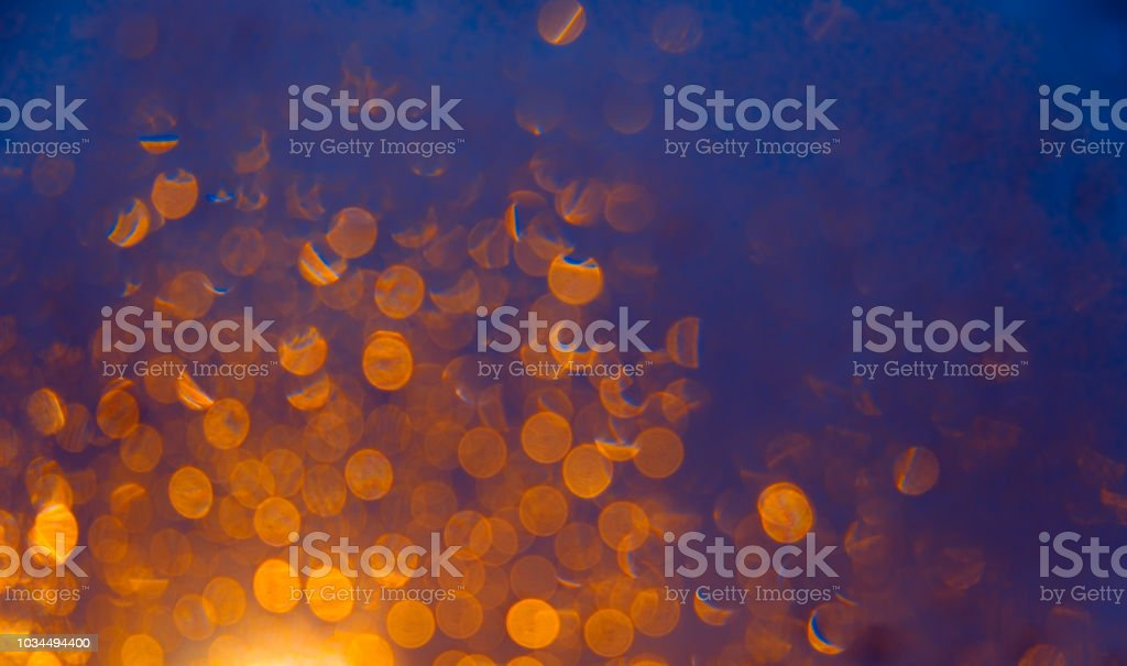 Luzes de fundo desfocado com bokeh laranja sobre fundo azul escuro - foto de acervo