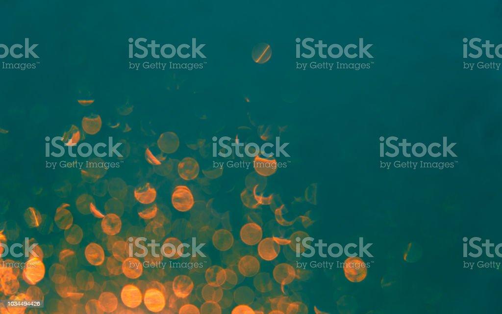Luzes de fundo desfocado com bokeh laranja sobre fundo verde-azulado - foto de acervo