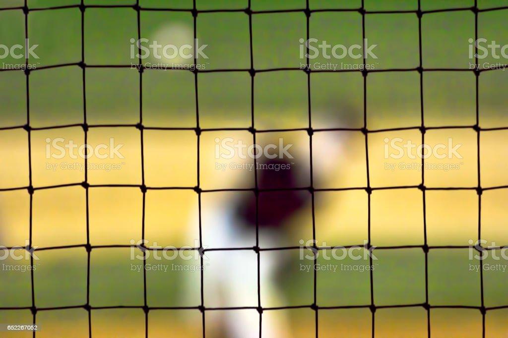Blurred Baseball Pitcher Seen Through Netting stock photo