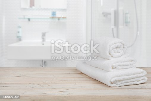 618327092istockphoto Blurred bathroom interior background and white spa towels on wood 618327092