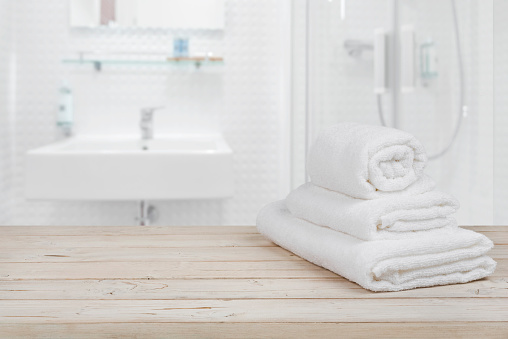 618327092 istock photo Blurred bathroom interior background and white spa towels on wood 618327092