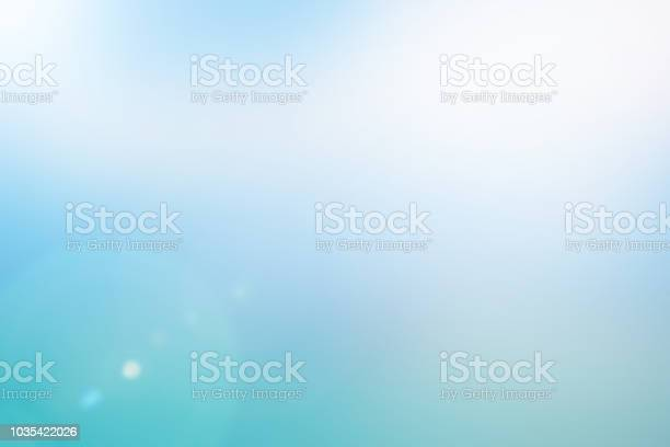 Photo of blurred beautiful natural morning sky in pastel tone color background with lens ray flare flash light.