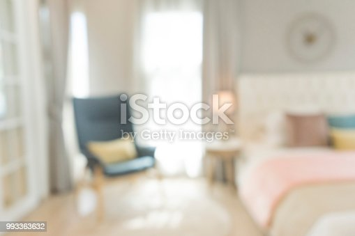 blurred bedroom with pillows and doll on white bed , use for background