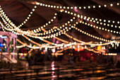 Blurred beer tent, tables, benches, blurry decorative light, London, UK.