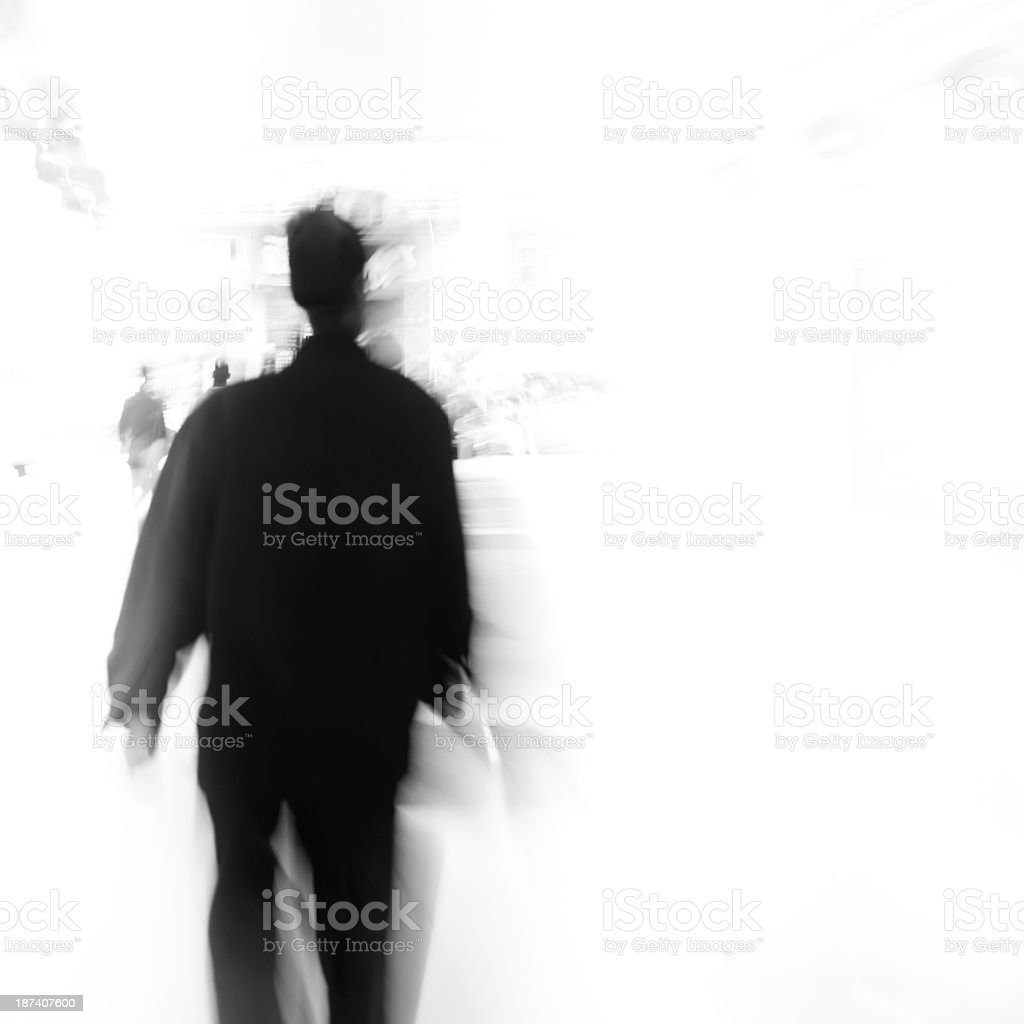 A blurred black figure on a white background stock photo
