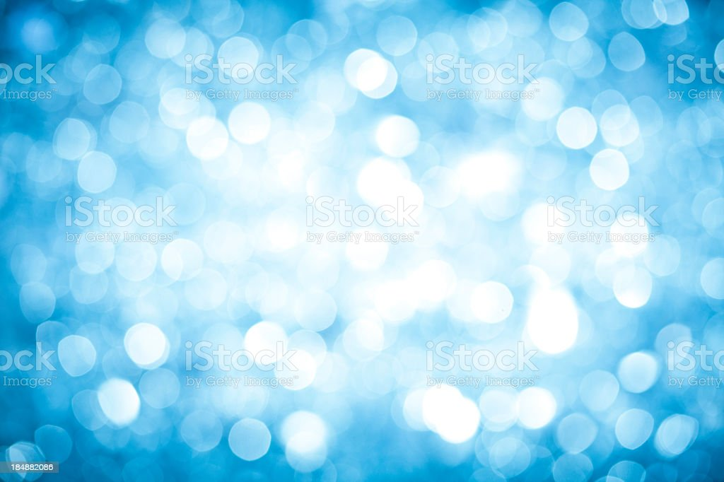 Blurred blue sparkles background with darker corners and bright center. stock photo