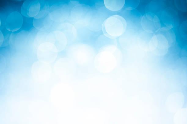 Blurred blue sparkles on white stock photo