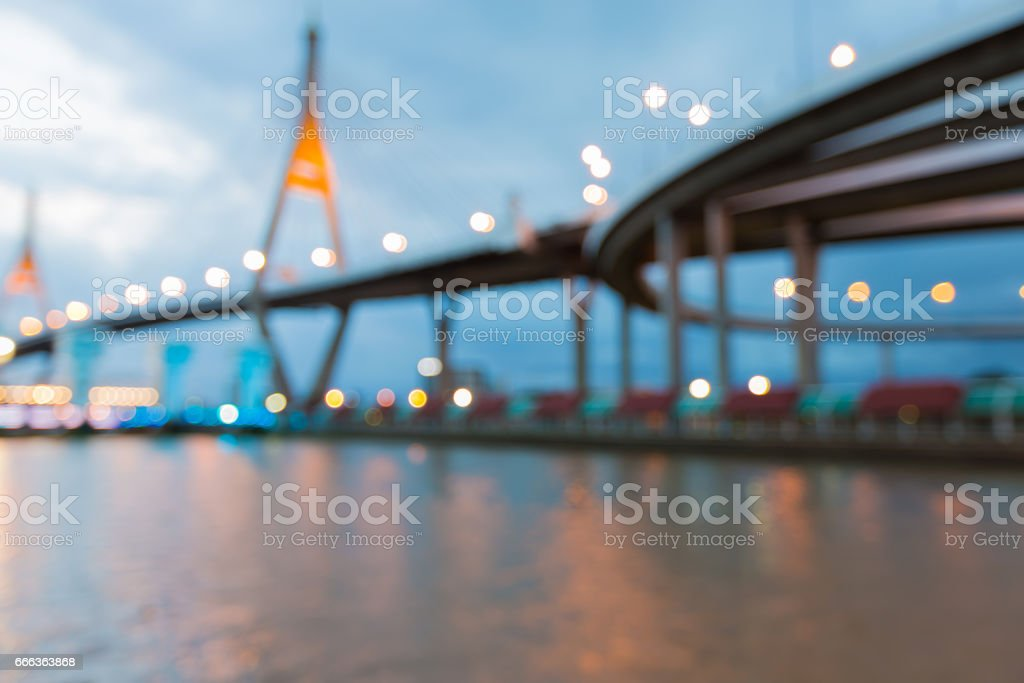 Blurred bokeh light Higway and suspension bridge river front stock photo