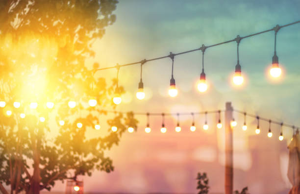blurred bokeh light on sunset with yellow string lights decor in beach restaurant - summer стоковые фото и изображения