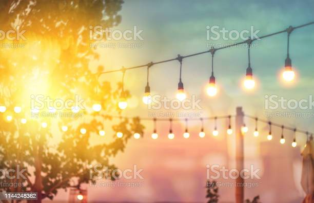 Photo of blurred bokeh light on sunset with yellow string lights decor in beach restaurant
