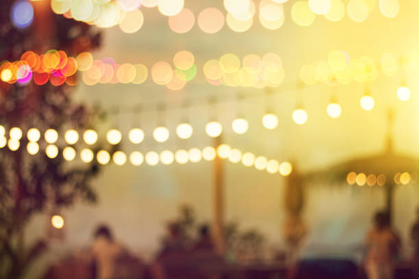 blurred bokeh light on sunset with yellow string lights decor in beach restaurant stock photo