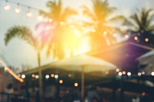 blurred bokeh light on sunset with yellow string lights decor in beach restaurant
