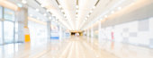 istock Blurred bokeh panoramic banner background of exhibition hall or convention center hallway. Business trade show event, modern interior architecture, or commercial tradeshow conference seminar concept 1047189958