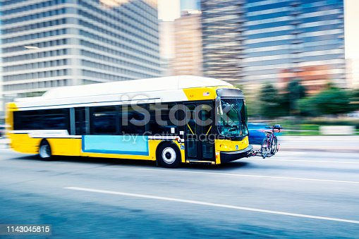 Photo of a blurred bus on a street of Dallas.