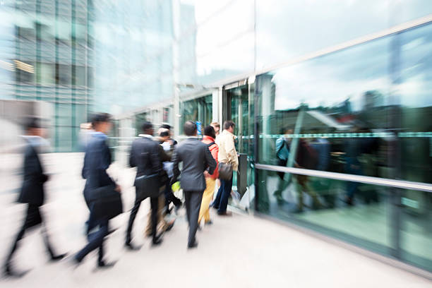 Blurred Business People Entering Office Building Through Glass Doors blurred view of business people walking through glass door,click here to view more related images: entering stock pictures, royalty-free photos & images