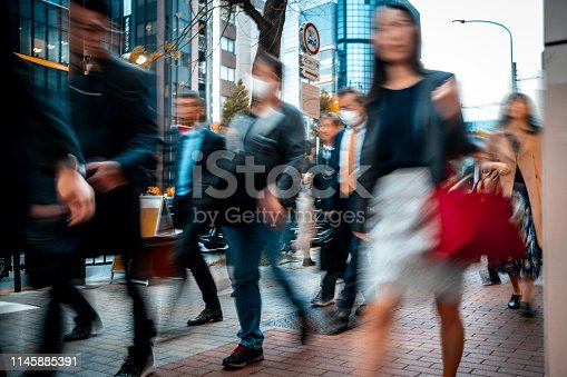 1146224410istockphoto Blurred business people on their way from work 1145885391