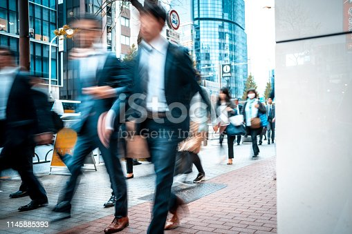 1146224410istockphoto Blurred business people on their way from work 1145885393