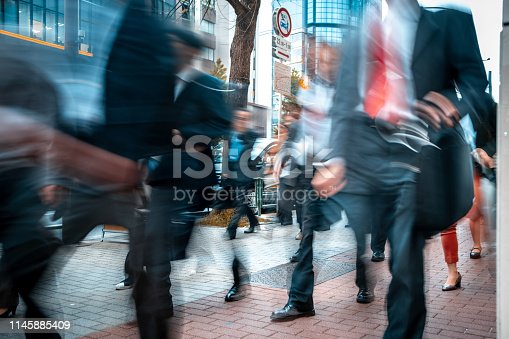 1146224410istockphoto Blurred business people on their way from work 1145885409
