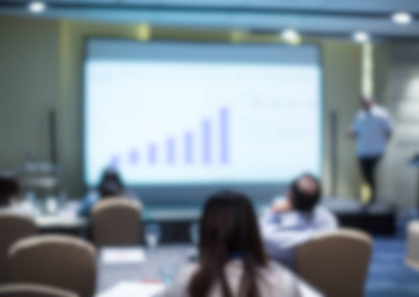 Blurred business presentation with corporate speaker near blank white screen. Seminar concept background with executive leading workshop in conference hall. Presenter in lecture to audience. Blurred presentation scene with bokeh electrical outlet stock pictures, royalty-free photos & images