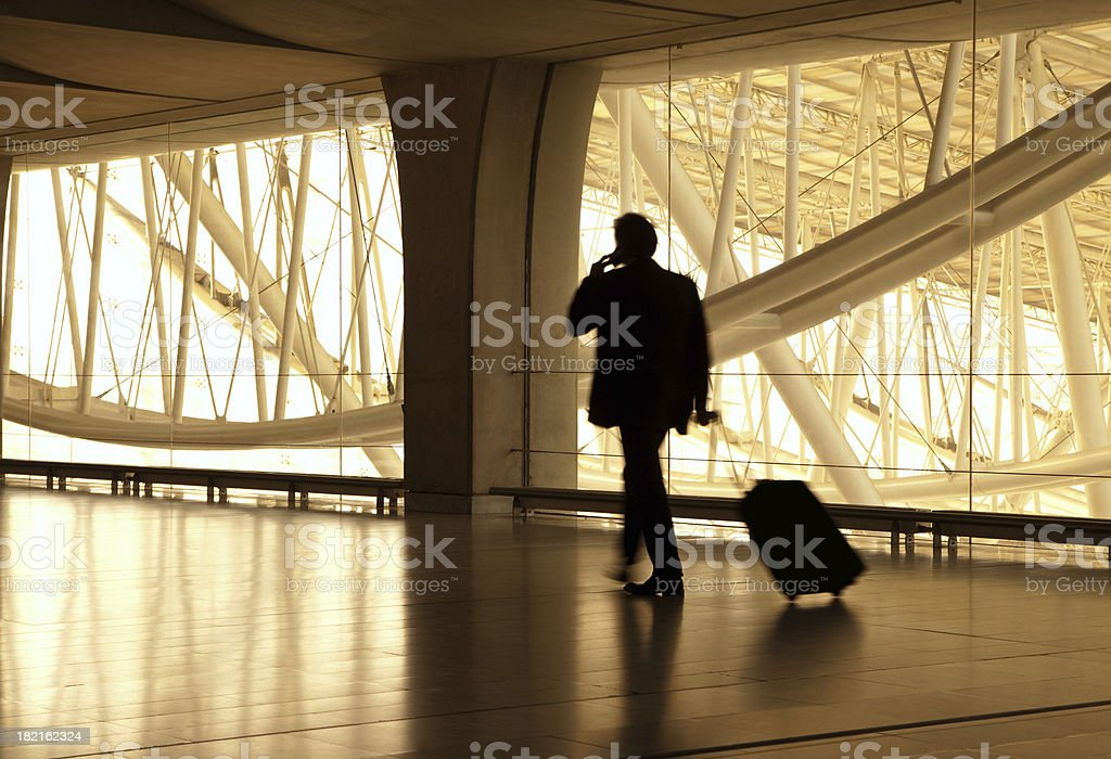 Blurred Businessman at Airport, Pulling Suitcase, Using Mobile Phone stock photo