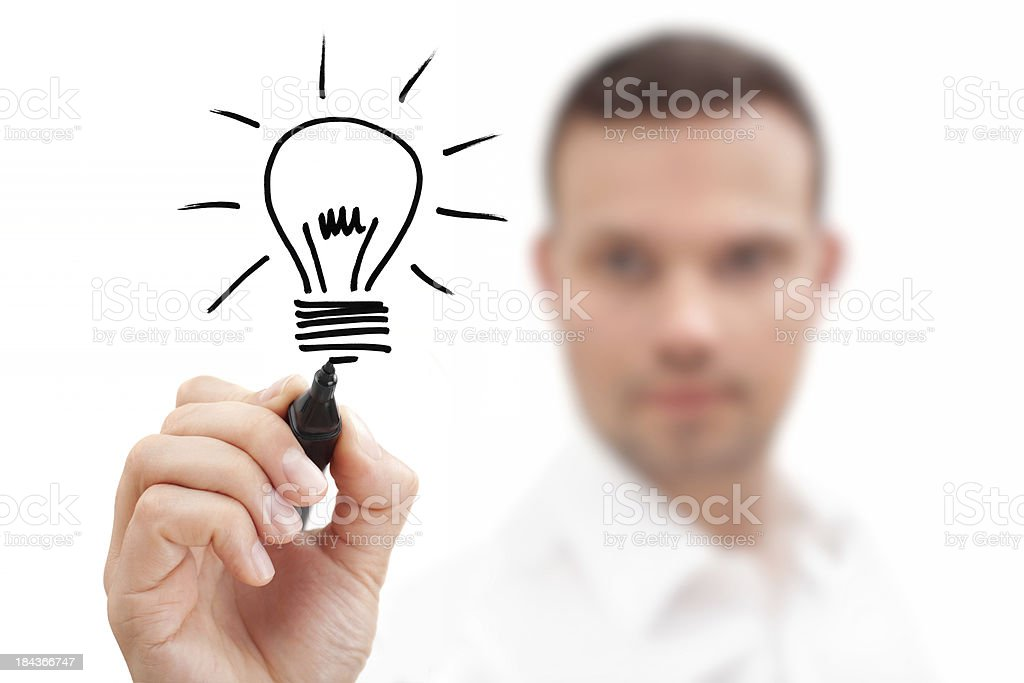 Blurred businessman drawing a lightbulb showing an idea Businessman drawing a bulb on a virtual whiteboard. Metaphor for Ideas and Inspiration. Adult Stock Photo
