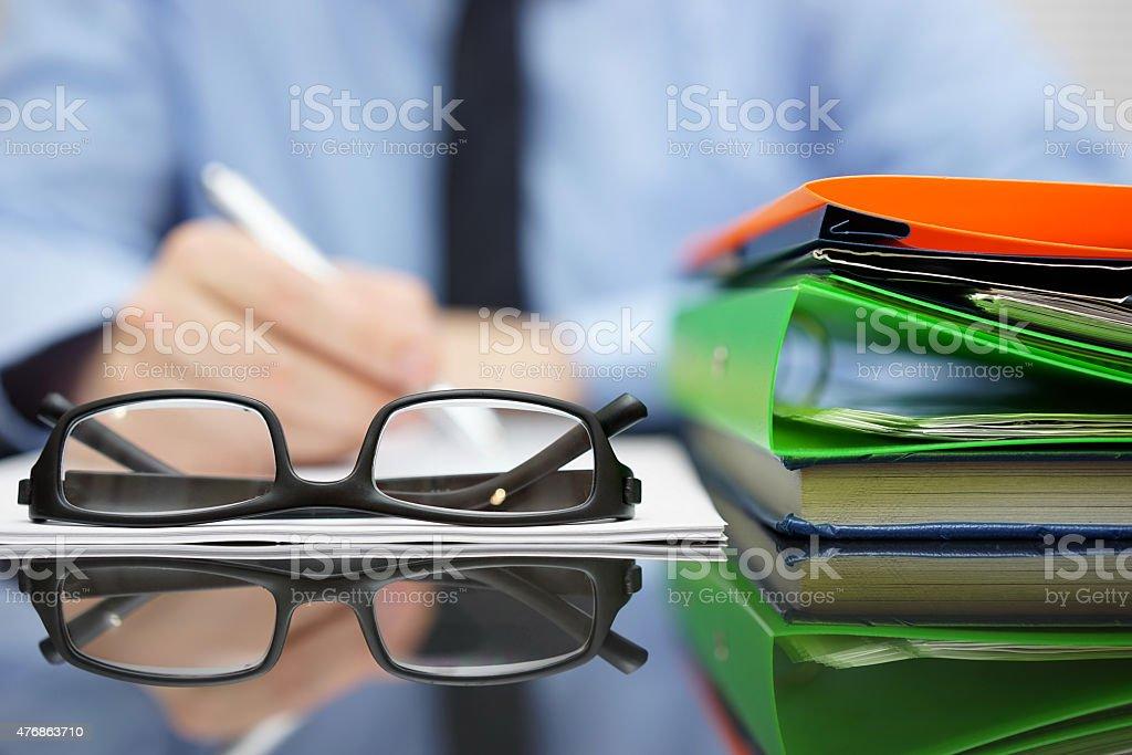 Verschwommene Geschäftsmann Schreiben Dokument ist, Fokus auf Brille und Ordner Lizenzfreies stock-foto