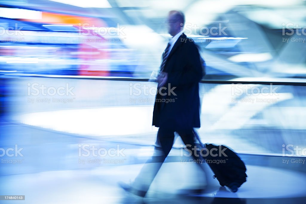 Blurred Businessman Pulling Suitcase Through Modern Interior stock photo