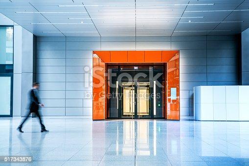 istock Blurred businessmen walking inside a modern building 517343876