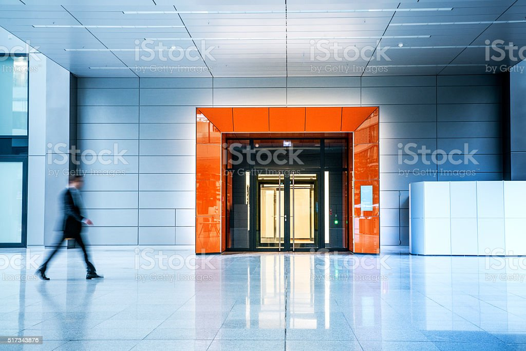 Blurred businessmen walking inside a modern building stock photo